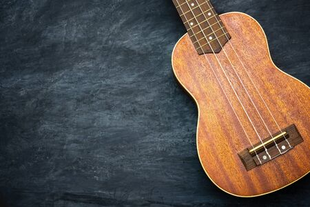 Ukulele on black cement background. Body and bridge of ukulele parts. Copy space for text. Concept of summer ukulele or Hawaiian musical instruments. Imagens - 132061168