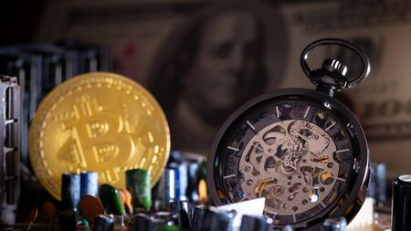 Pocket watch and gold bitcoin with dollar banknote on computer mainboard in darkness background.