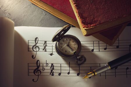 Music notes and old book with pocket watch on wooden table background in morning light. Writing chords by vintage pen. Closeup and copy space for text. Concept of Music lovers.