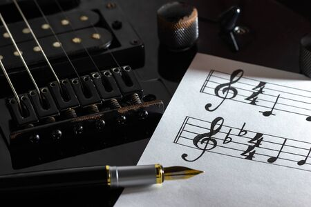Music note and vintage pen on black electric guitar in darkness. Concept of rock music creative. Imagens