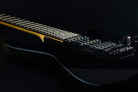 Black electric guitar in darkness. Concept of rock music style.