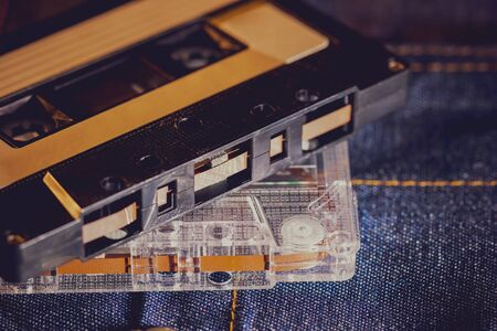 Cassette tape audio on jeans fabric in darkness. Concept of vintage 90s music player.