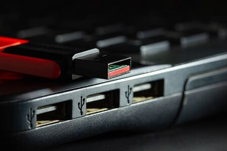 Flash drive in USB port of computer notebook in darkness. Concept of technological advances in computer data recording systems.