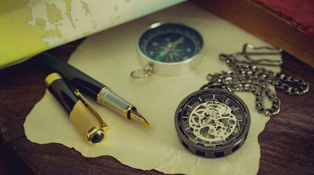 Pocket watch with old books and pen with paper map on the table by the window. Concept of travel planning. Reklamní fotografie
