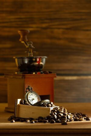 Coffee bean and pocket watch. Manual grinder on table in morning. Concept of coffee time.