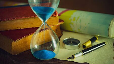 Sand clock with old books and pen with paper map on the wooden table. Concept of travel planning.