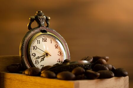Coffee bean and pocket watch in manual grinder on table. Closeup and copy space. Concept of coffee time in morning. Imagens