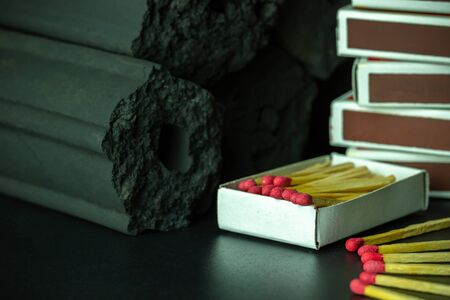 Box of matches and Carbon activated bamboo charcoal on dark background. Concept of fuel for living in the forest. Closeup and copy space.