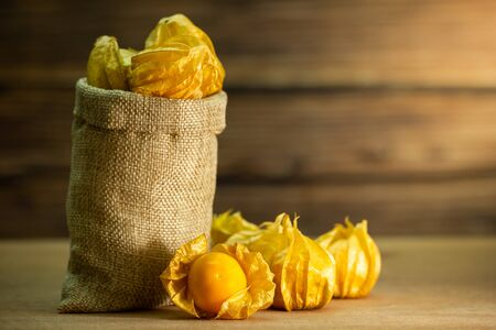 Cape gooseberry in burlap bags. Concept of health care or herb. Closeup and copy space for text. Imagens