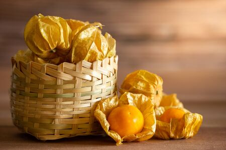 Cape gooseberry in bamboo basket. Concept of health care or herb. Closeup and copy space for text.