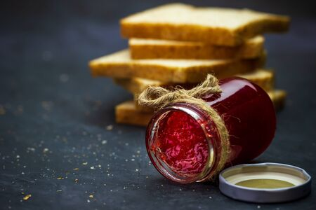 Strawberry jam bottle and whole wheat bread are stacked on a black background. Concept of breakfast and healthy food.