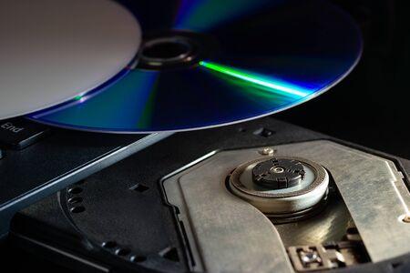 CD sul computer notebook cd rom nelle tenebre. Concetto di progressi tecnologici nei sistemi di registrazione dei dati informatici.