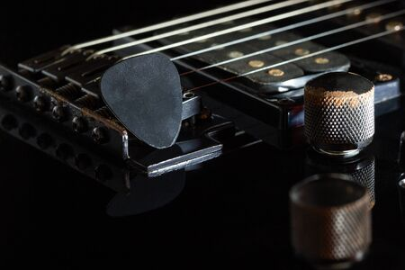 Black guitar pick on black electric guitar in darkness. Concept of rock music style.