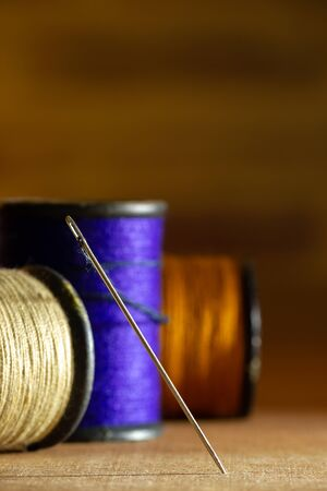 Needle and threads on wooden table. Closeup and copy space for text. Concept of tailor or Designer. Imagens