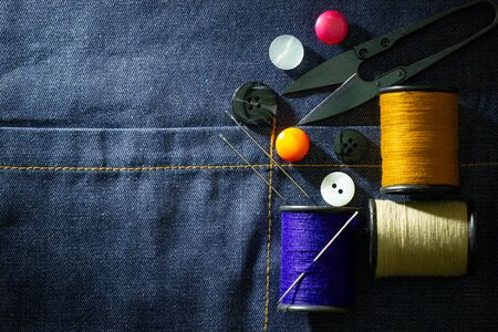 Needle and threads against plastic button and thread cutting scissors on jeans fabric. Top view and copy space for text. Concept of tailor or Designer.