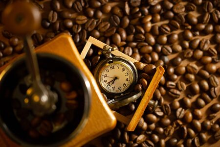 Coffee bean and pocket watch the tray of manual grinder on table. Top view and copy space. Concept of coffee time in morning. Imagens