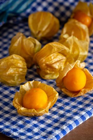 Cape gooseberry on blue tablecloth. Concept of health care or herb.