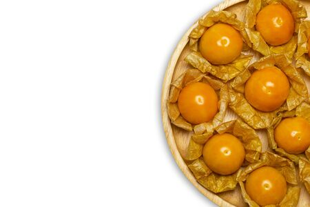 Cape gooseberry on wooden dish in white background. Concept of health care or herb. Top view and copy space for text.