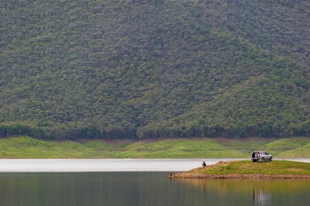 Men sitting and fishing on island at the dam among the mountains.