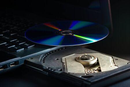 CD sur le cd-rom de l'ordinateur portable dans l'obscurité. Concept d'avancées technologiques dans les systèmes d'enregistrement de données informatiques.