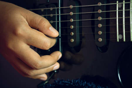 Guitarist is rehearsing playing black vintage electric guitars. Closeup  girl's hand is holding the pick and putting it on guitar string in dark studio. Concept of musical instruments and rock music.