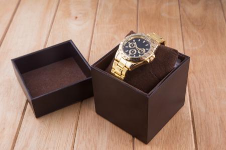 mans watch: caja con reloj de lujo en fondo de madera