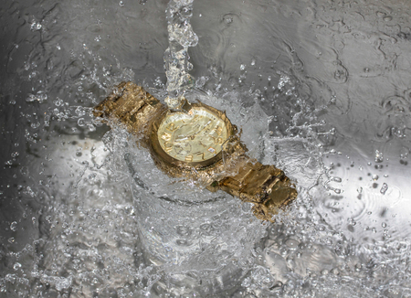 pour water: Pour water into the wristwatch - Waterproof wristwatch concept.