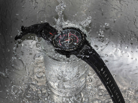 waterproof: Pour water into the wristwatch - Waterproof wristwatch concept.