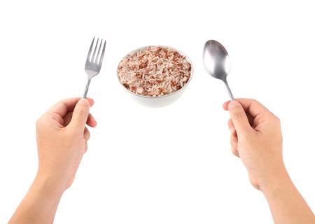 cuchara: La mano sostiene una cuchara con el cuenco de arroz aislado en un blanco.