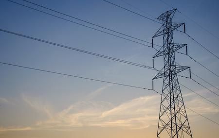 torres el�ctricas: Las torres de electricidad contra anaranjado y azul puesta del sol Foto de archivo