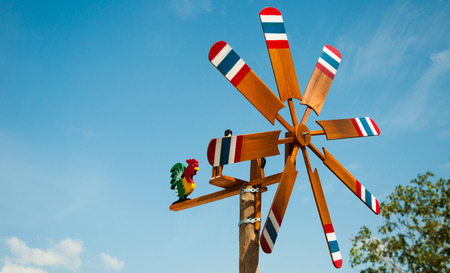 Wind turbine wooden paint a flag of Thailand on blue sky background