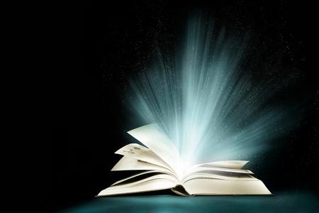 Opened magic book with magic light Imagens