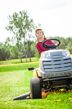 Boy sitting on the mower and cutting the grass
