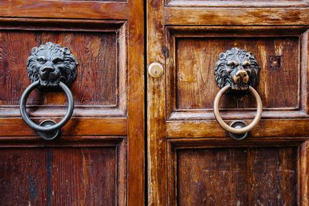 Front view of a vintage door knocker on a solid old wooden door. Stock Photo