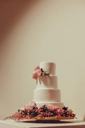 Weiße Hochzeitstorte verziert mit Rosen auf dem Tisch.