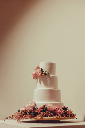 White wedding cake decorated with roses on the table.