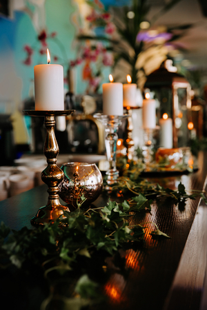 Romantic table setting decorated with burning candles and green ivy leaves.