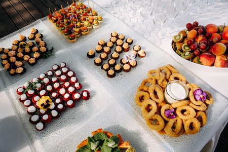 Banquet table with different canapes and fruits. Imagens - 121889715