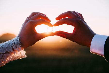 Deux personnes mariées tenant des alliances au coucher du soleil.