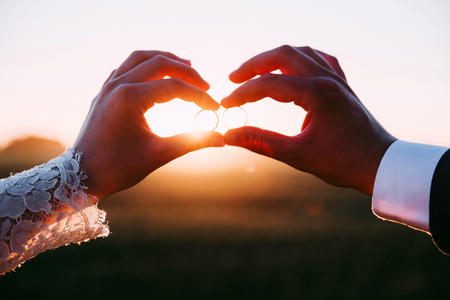 Two married people holding wedding rings at sunset.