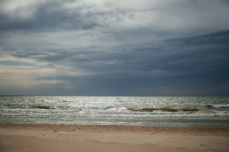 Dramatic beach with dark clouds before a storm.