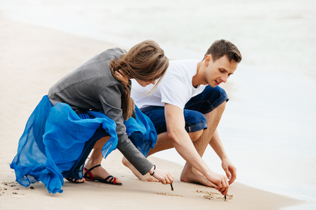 Young couple on the beach drawing in sand.