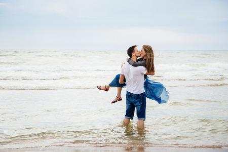 Coppia di innamorati sulla spiaggia. Uomo che tiene una donna nelle sue mani.
