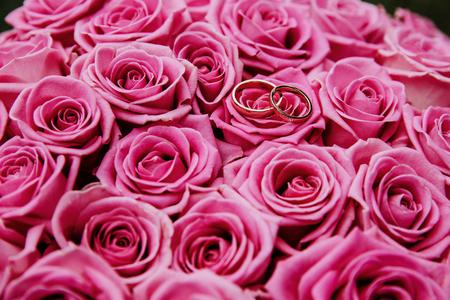 Due fedi nuziali poste sul bouquet di rose rosa. Immagine ravvicinata.