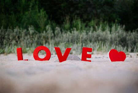 The 3D letters of LOVE arranged in sand.