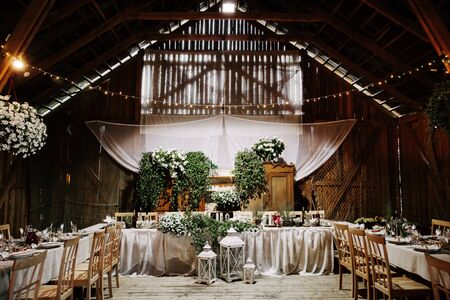 Banquet rustic hall with decorated tables.