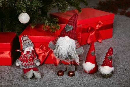 Decorated Christmas tree with presents arranged under the tree. Close up image of three small dwarfs.