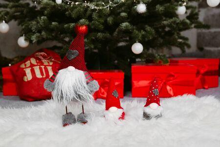 Geschmückter Weihnachtsbaum mit Geschenken, die unter dem Baum angeordnet sind. Nahaufnahme Bild von drei kleinen Zwergen.