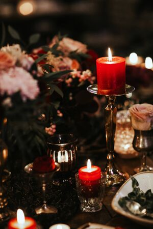 Beautiful, decorated table with flower decorations and red candles.