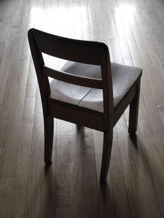shadowed: A shadowed chair ahead a light reflection on a wood floor.